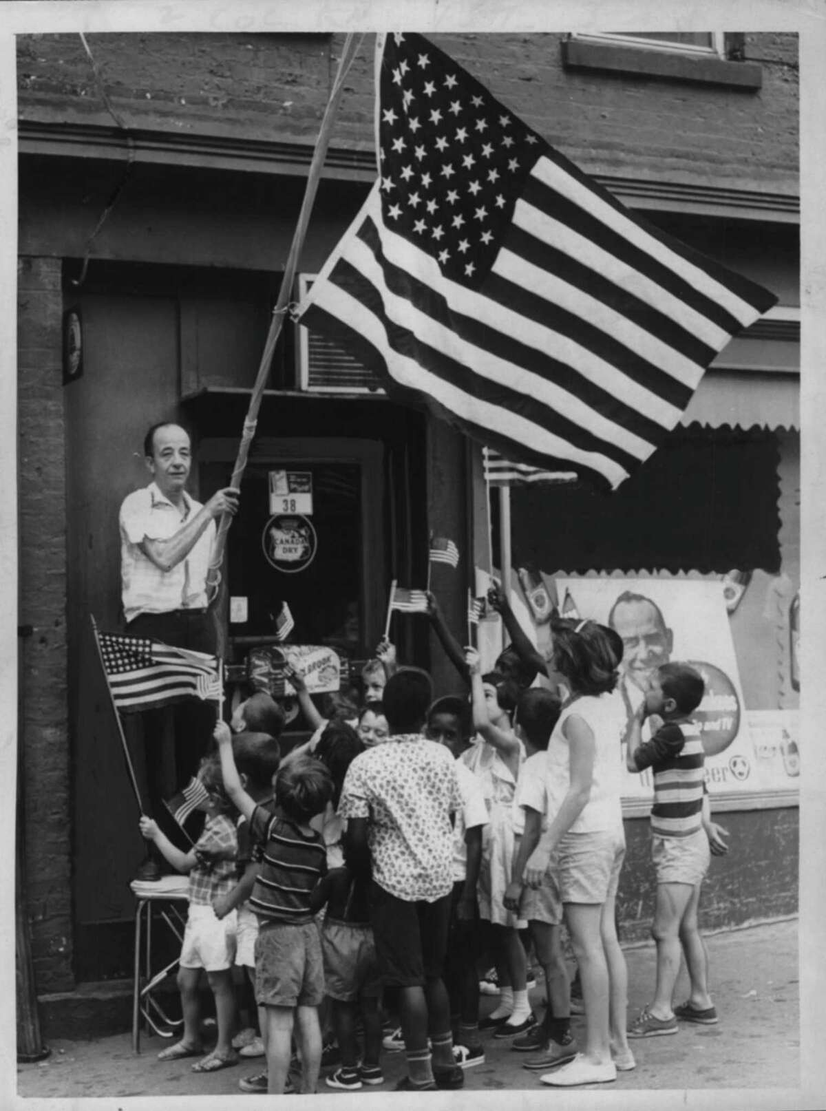 Albany, New York - Albany grocer Joseph Russo, a strong believer in displaying the colors on patriotic occasions, begins his July 4th weekend with some flag-waiving today in front of his store at 28 Park Avenue. Neighborhood children wave their own flags to join Mr. Russo's early celebration of Independence Day. July 03, 1964 (Knickerbocker News Staff Photo/Times Union Archive)