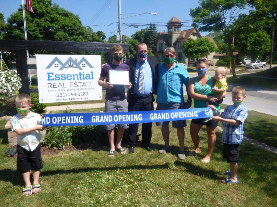 Therran Ferguson and his family pose for pictures following the ribbon-cutting ceremony for Essential Real Estate on Wednesday. Photo: Scott Fraley/News Advocate
