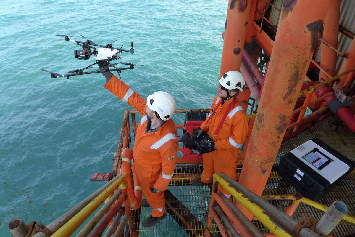 Cyberhawk workers launch a drone to inspect an offshore oil platform.