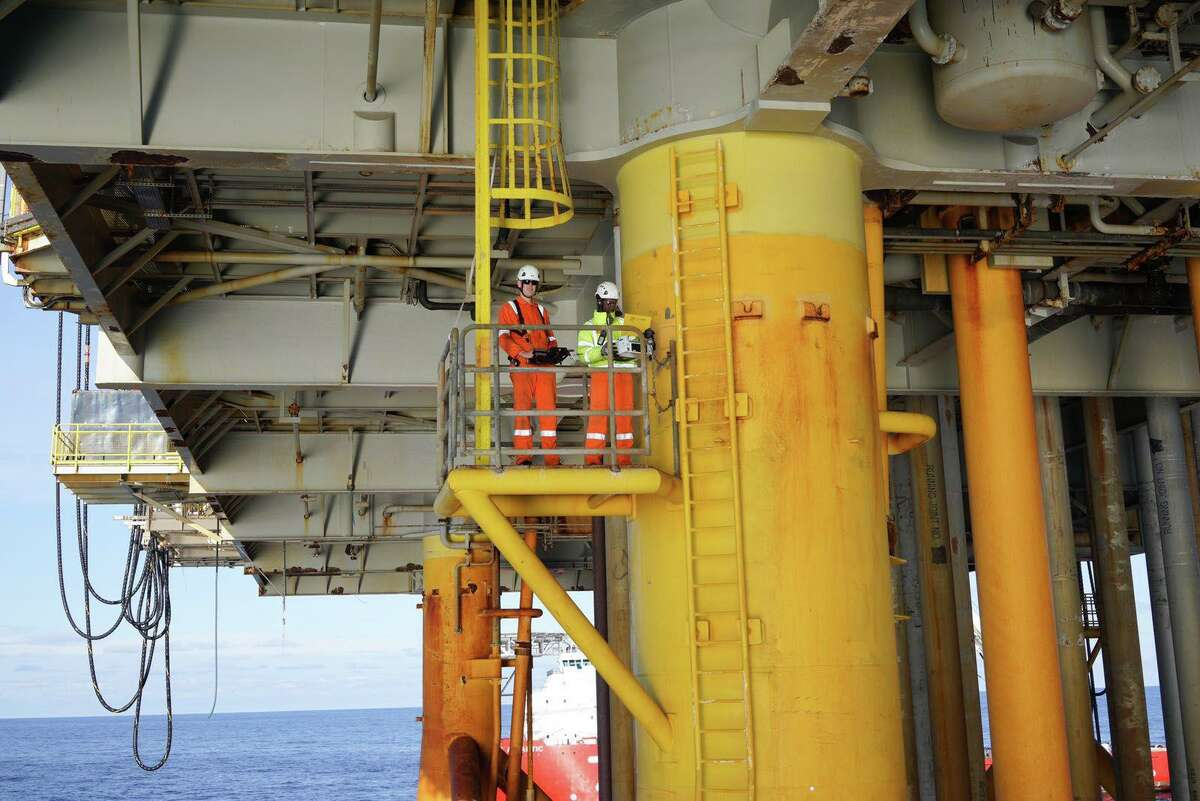 Cyberhawk workers maneuver a drone inspecting the underdeck of an offshore oil platform.