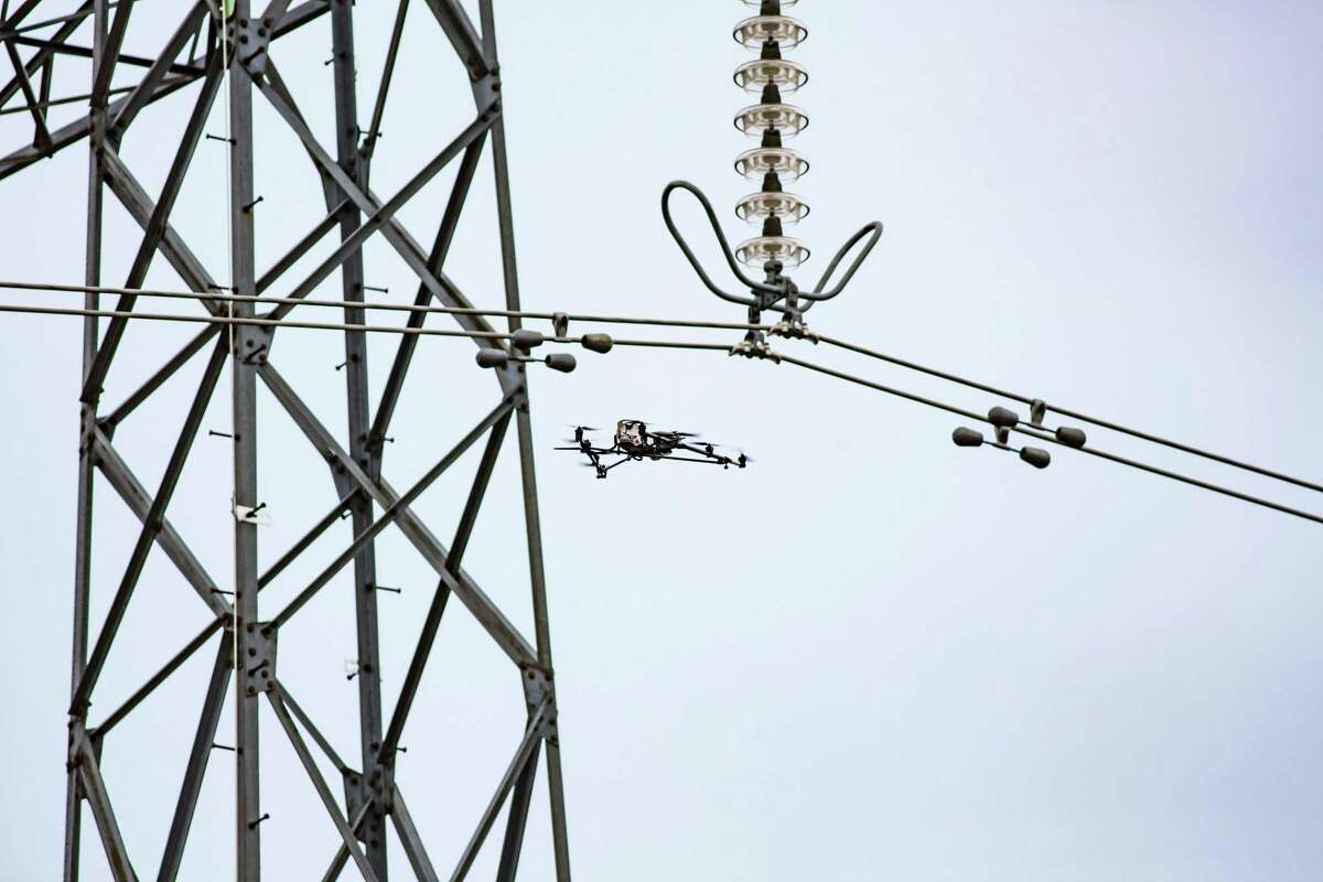 A Cyberhawk drone inspects transmission lines.