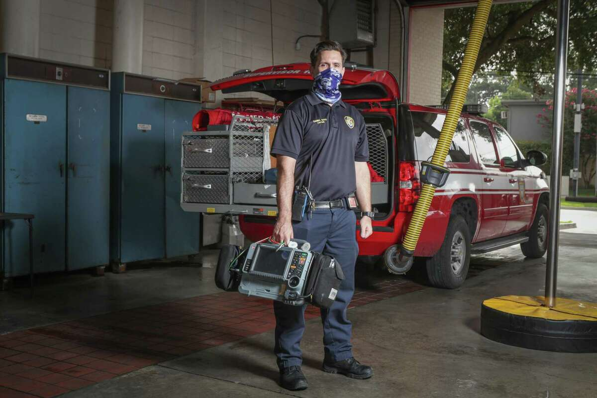Houston Fire Department Capt. Daniel Soto poses behind his vehicle he uses to respond to emergencies Friday, July 3, 2020, in Houston.
