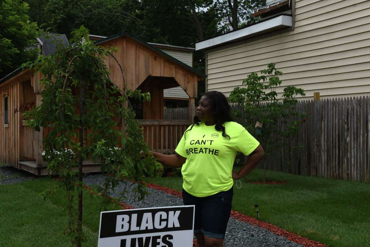 Kizzy Williams, the owner of Allie B?•s Cozy Kitchen, looks at one of the a cherry trees planted on the lot she bought at the corner of Quail and First streets on Friday, July 3, 2020, in Albany, N.Y. Williams is turning her lot into a cultural hub. She hopes it will inspire Black ownership of land and homes. (Will Waldron/Times Union)