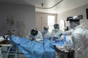 Doctors and nurses wearing protective gear treat a patient in the Covid-19 intensive care unit (ICU) at the United Memorial Medical Center (UMMC) in Houston, Texas, U.S., on Monday, June 29, 2020. Covid-19 cases and hospitalizations have spiked since Texas reopened eight weeks ago, pushing intensive-care wards to full capacity and sparking concerns about a surge in fatalities as the contagion spreads. Photographer: Go Nakamura/Bloomberg