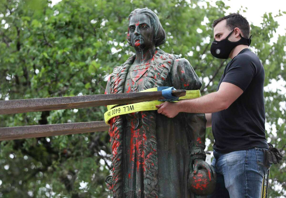 Workers hired by the City of San Antonio remove the defaced statue of Christopher Columbus from Columbus Park on July 1.