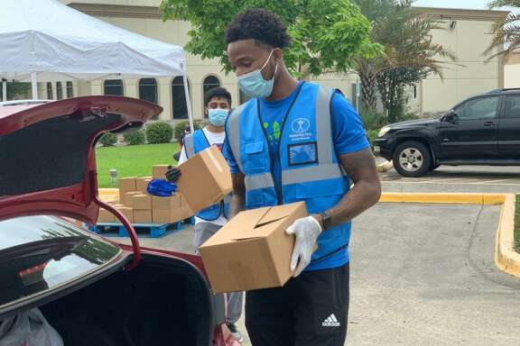 Demetrius Levarity, a friend of the organization and volunteer, helps distribute packages of food. An estimated 500 cars stopped by the Baitus Samee Mosque in a span of about three hours at a food pantry hosted by the Ahmadiyya Muslim Youth Association, June 27, where roughly 10,000 pounds of food were distributed.
