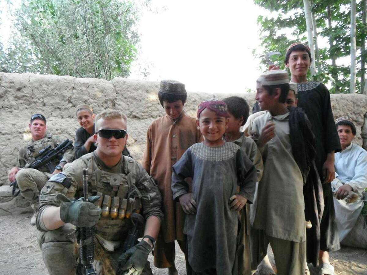 James O. Twist poses with local children during his deployment in Afghanistan in 2012. MUST CREDIT: Courtesy of the Twist family