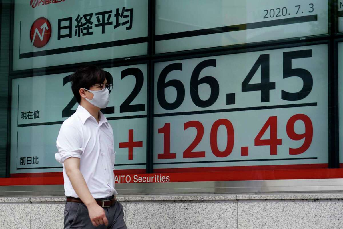 A man walks past an electronic stock board showing Japan's Nikkei 225 index at a securities firm in Tokyo Friday, July 3, 2020. Markets advanced in Asia on Friday following a Wall Street rally driven by strong jobs data. (AP Photo/Eugene Hoshiko)