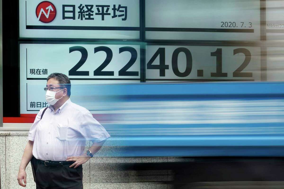 A man stands near an electronic stock board showing Japan's Nikkei 225 index at a securities firm as a track passes by in Tokyo Friday, July 3, 2020. Markets advanced in Asia on Friday following a Wall Street rally driven by strong jobs data. (AP Photo/Eugene Hoshiko)