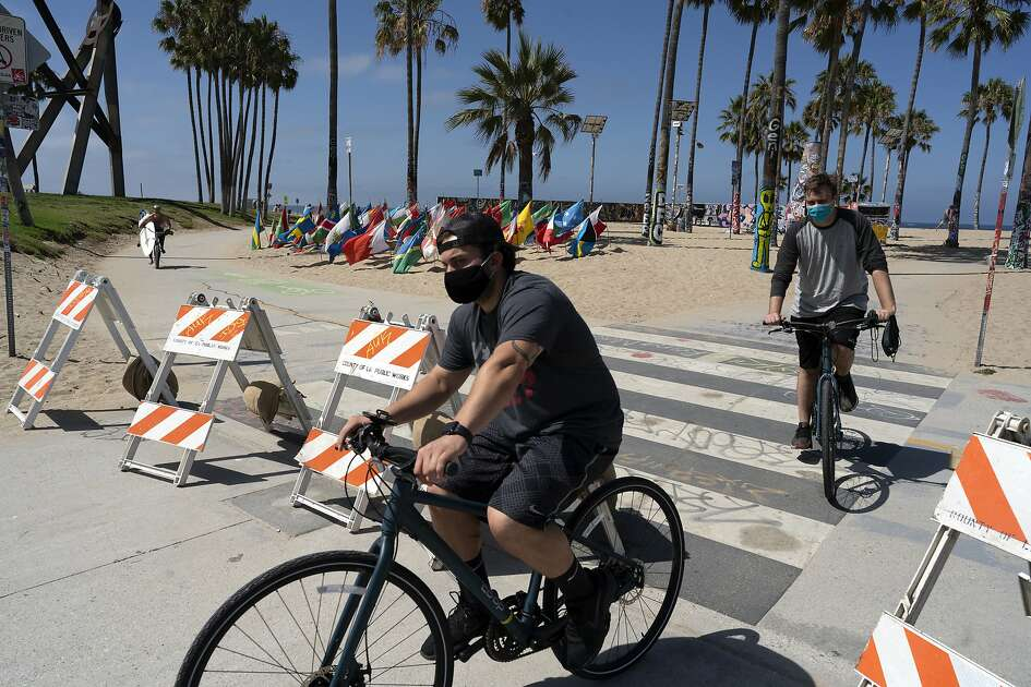 Cyclists wearing masks to protect from coronavirus cross a closed section of Venice beach on Friday, July 3, 2020 in Los Angeles. California's governor is urging people to wear masks and skip Fourth of July family gatherings as the state's coronavirus tally rises. All L.A. County beaches are closed from July 3 through July 6, to prevent dangerous crowding. Rates of COVID-19 infections and hospitalizations have soared in the past two weeks after falling last month. (AP Photo/Richard Vogel)