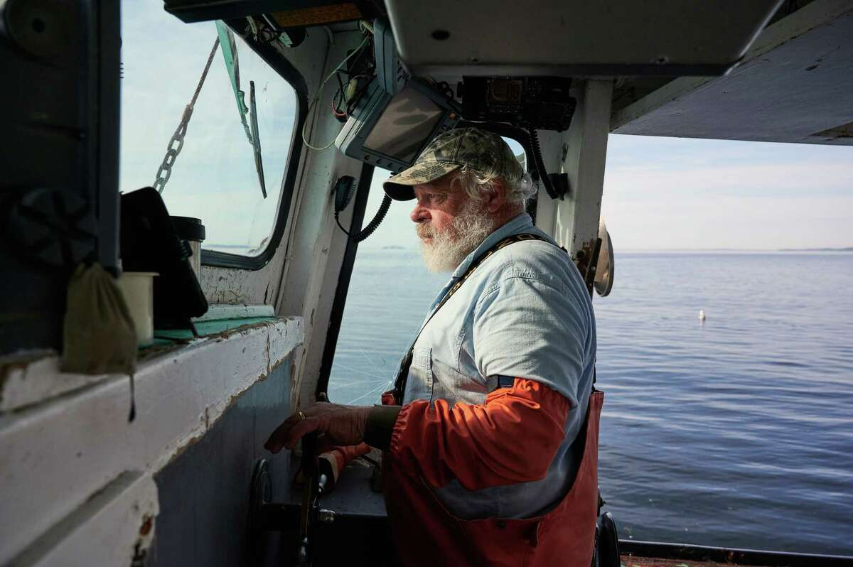 Mike Hutchings, who has fished the waters off Maine for more than 50 years, pilots his boat while harvesting lobsters off Lincolnville on Saturday, June 27, 2020. The statea€™s lobster industry, already struggling before the coronavirus, could be crippled as tourism dries up, leaving boatloads of crustaceans and no one to eat them. (Tristan Spinski/The New York Times)