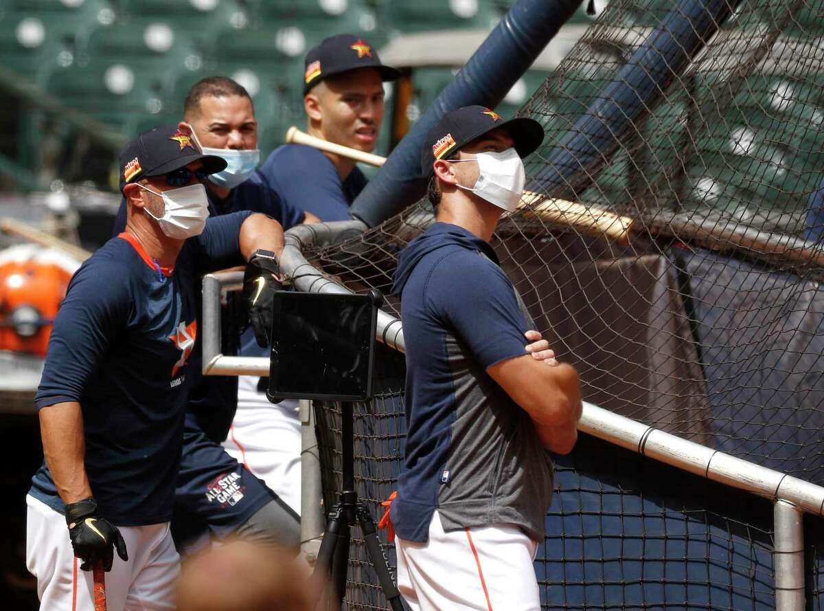 Jason Kanzler, Joe Espada, and Alex Cintron wear masks behind the batting cage with shortstop Carlos Correa during the first day of the Houston Astros Summer Camp at Minute Maid Park, Friday, July 3, 2020, in Houston.