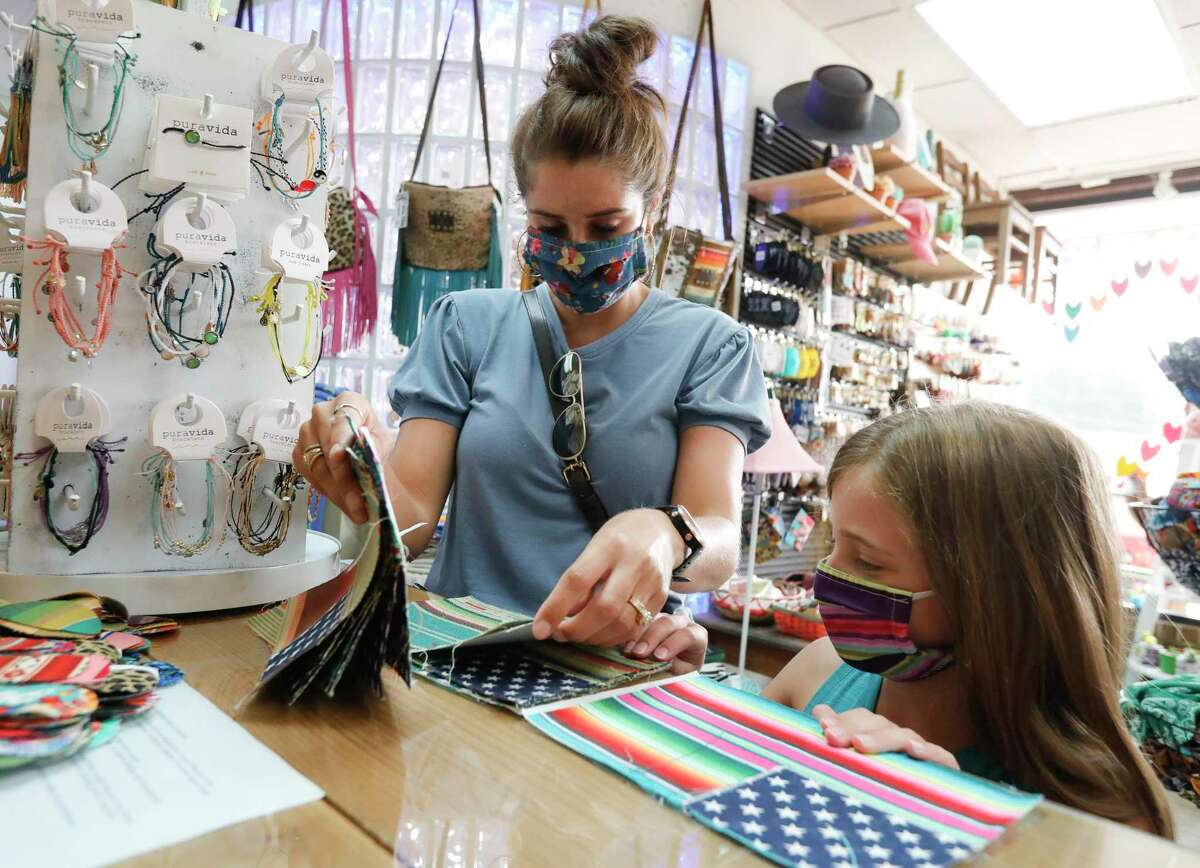 Ashley Russell, left, picks through face mask fabric with her eight-year-old daughter, Charly, at Sweet Texas Treasures Boutique, Friday, July 3, 2020, in Montgomery. Gov. Greg Abbott's statewide face covering order, which affects most Texans, went into affect at noon in an effort to slow the spread of COVID-19.