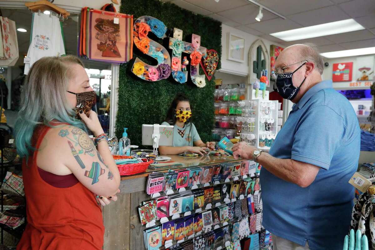 Sweet Texas Treasures Boutique owner Morgan Calhoun, left, works with customer Gerald Goolsby as he requests a custom face mask, Friday, July 3, 2020, in Montgomery. Gov. Greg Abbott's statewide face covering order, which affects most Texans, went into affect at noon in an effort to slow the spread of COVID-19.