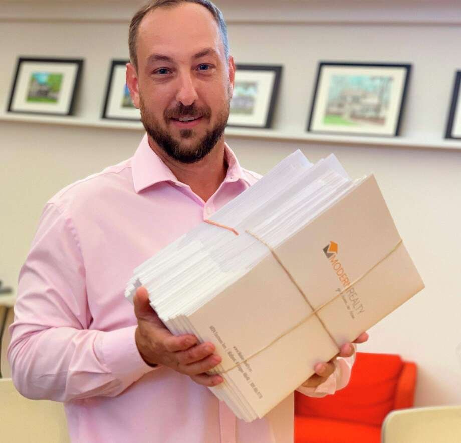 Modern Realty owner Logan Richetti, spokesman and broker for Village West Condominiums, holds the 46 individual contract documents on Friday after the 46 Village West owners unanimously agreed to developer Doug Loose's purchase offer. (Photo provided)