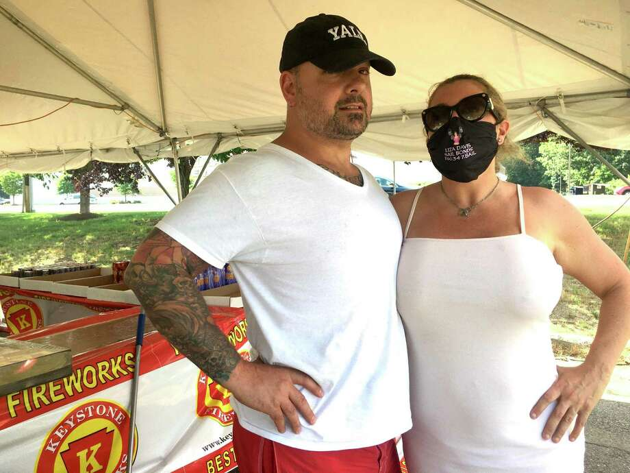 On Independence Day, attitudes about masks for coronavirus reflect the principles of the founding of the United States. Pictured are Massimo DeMedici and Liza Davis, in the bail bonds business, who have complex ideas about masks; and a scene in South Norwalk where a group of friends including A.J. Ibarrondo greeted one another with hugs. Photo: Dan Haar/Hearst Connecticut Media