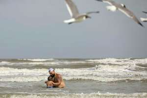 "Benjamin McCarthy plays with his son DeLuca, aged 15 months, Wednesday, July 1, 2020, at the beach in Galveston. City officials said the city will close its beaches to the public for the July 4th holiday weekend amid a spike in new coronavirus cases. ""I think more people are starting to get nervous,"" McCarthy said."
