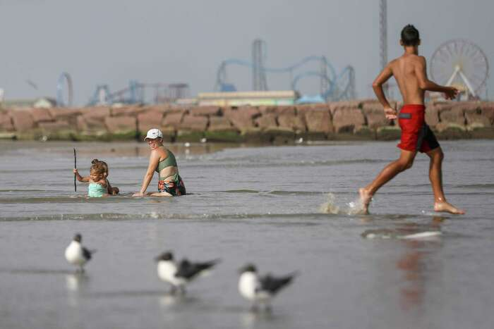 """Caitlin Morales looks back at her son as he runs by, as she plays with her daughters Hannah, left, 1, and Evelyn, 3, Wednesday, July 1, 2020, at the beach in Galveston. """"I feel that the beach is more comfortable than most other places we go visit,"""" Morales said. City officials said the city will close its beaches to the public for the July 4th holiday weekend amid a spike in new coronavirus cases."""