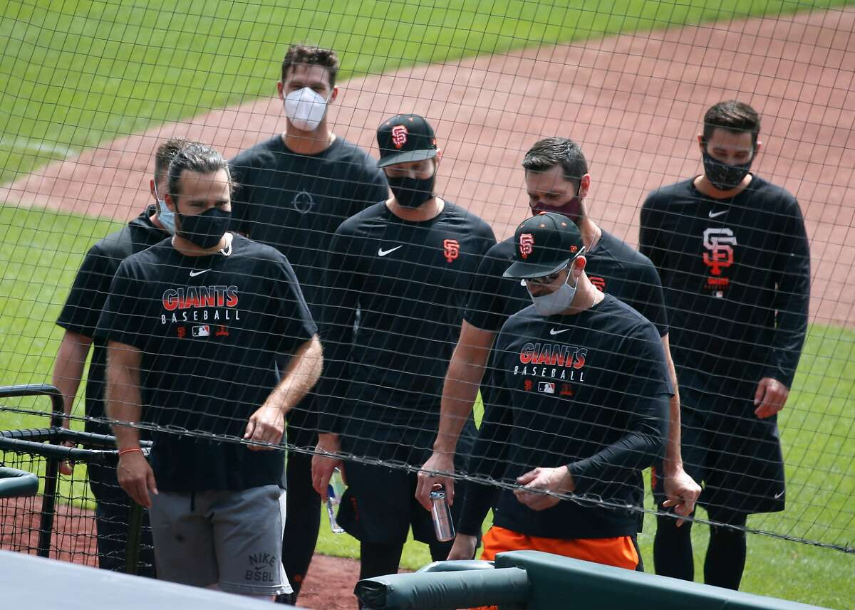Brandon Crawford (left) and other players walk into the dugout for the Giants first Spring Training workout during the coronavirus pandemic at Oracle Park San Francisco, Calif. on Friday, July 3, 2020.the Giants first Spring Training workout during the coronavirus pandemic at Oracle Park San Francisco, Calif. on Friday, July 3, 2020.