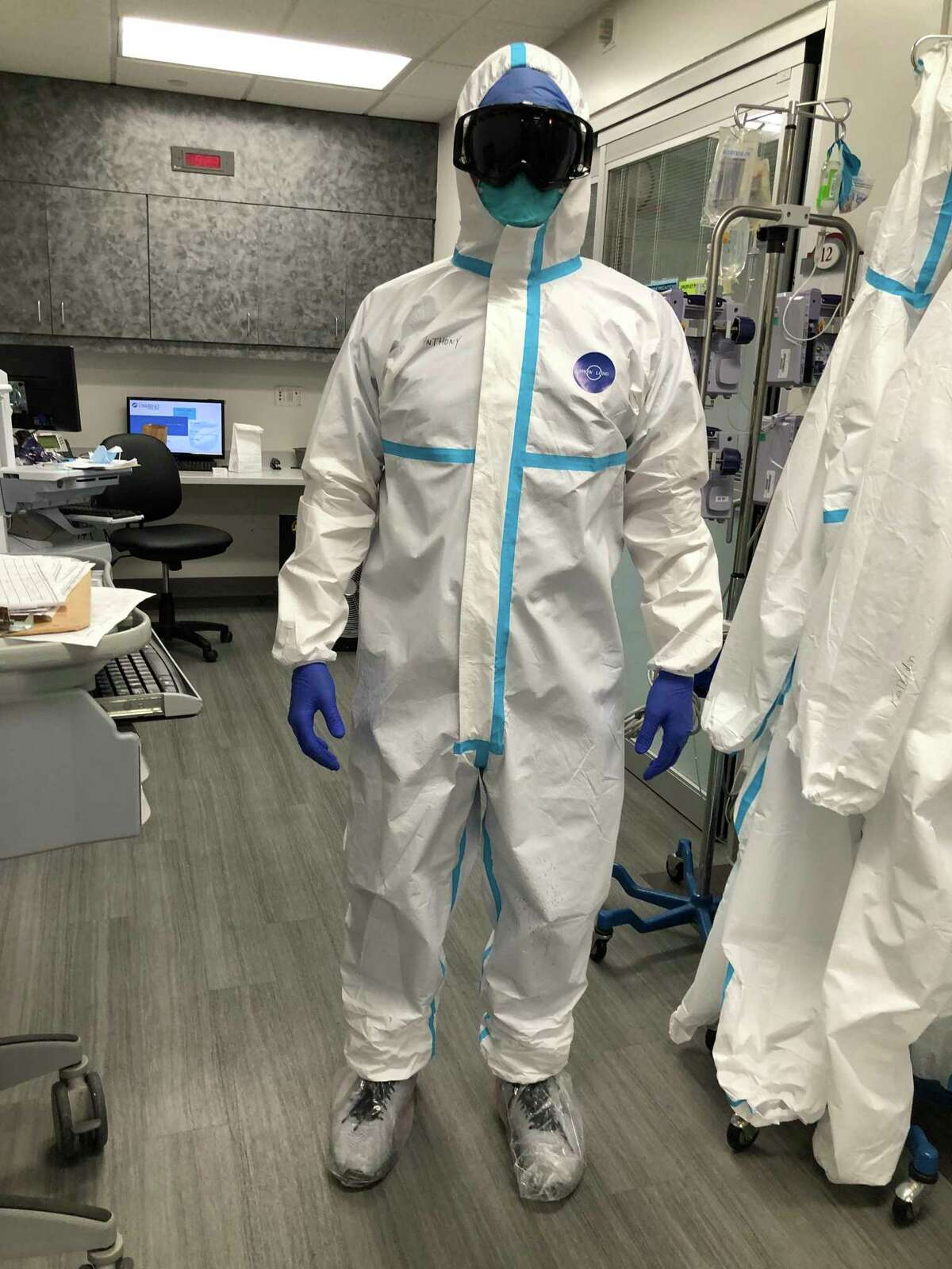 ICU Charge Nurse Anthony Lundquist dons full PPE at OakBend Medical Center's Jackson Street Intensive Care Unit.
