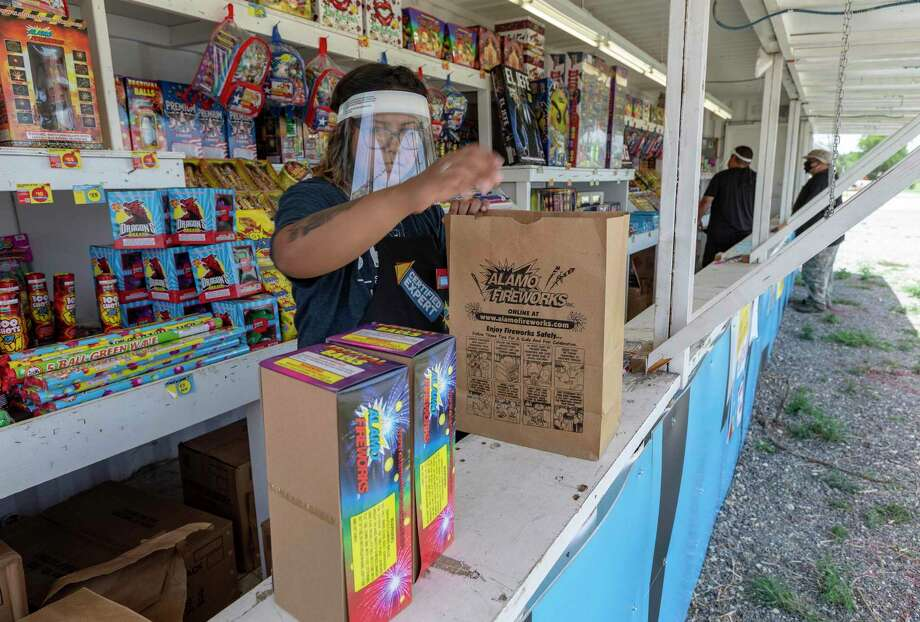 Cianna Cortez bags fireworks Thursday  for a customer at the Alamo Fireworks location in the 10400 block of O'Connor Road. Photo: William Luther /Staff / ©2020 San Antonio Express-News