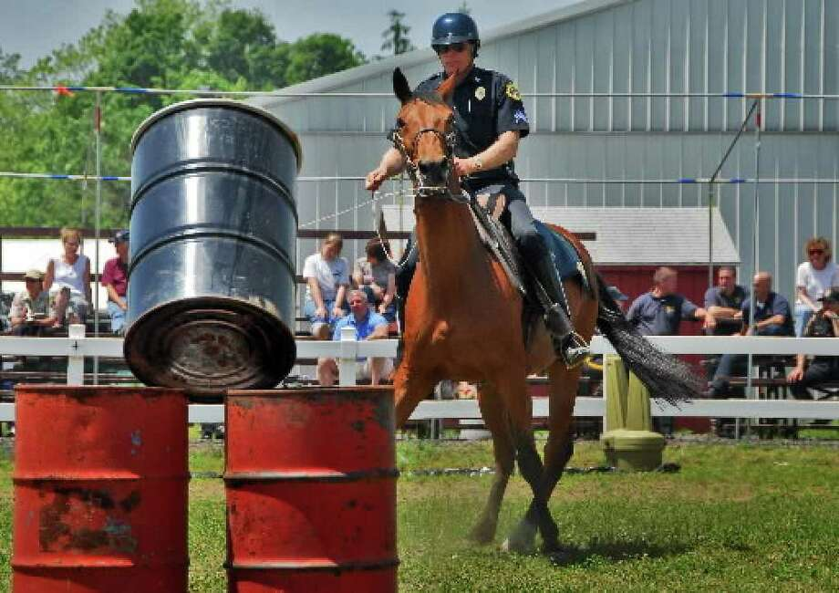 Saratoga Springs Police Sgt. Michael Chowske rides Jupiter in an obstacle course during mounted unit competition in 2006. A Cohoes man is charged with punching Jupiter in the face. (Times Union archive)