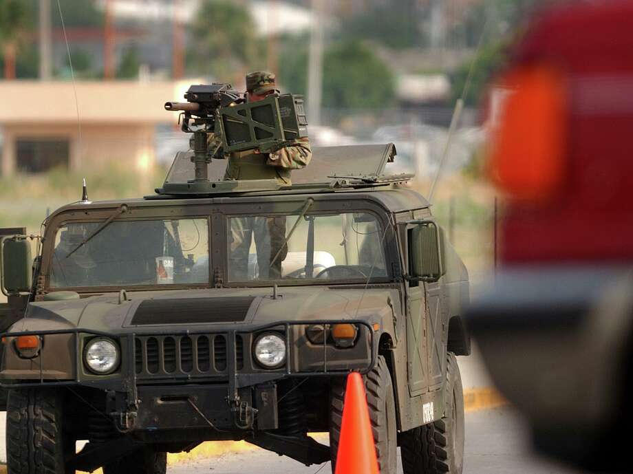 A soldier on a heavily armed Mexican Army humvee watches over traffic near the city's municipal police headquarters, which has been taken over by elements of the Mexican Army and the AFI, the Mexican equivalent of the FBI, n the wake of last week's shooting of the city's police chief. June 13, 2005. BLLY CALZADA Photo: BILLY CALZADA /SAN ANTONIO EXPRESS-NEWS / SAN ANTONIO EXPRESS-NEWS