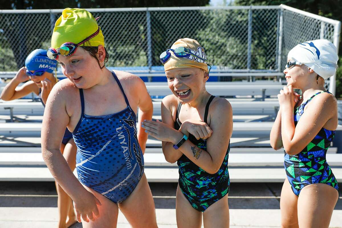 (L-r) Sydney Tumilty,8, Gwen Muldoon, 8, and Scarlett Benbow, 8 try to keep warm before jumping into the pool during swim camp at Soda Aquatic Center at Campolindo High School in Moraga, California on Thursday, July 2, 2020.