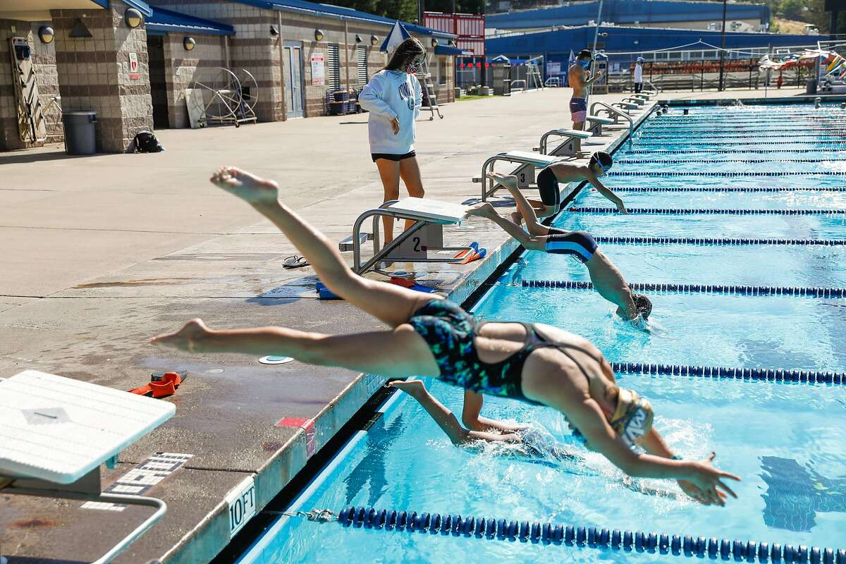 Teacher Sophia Riva (center) watches her students�s dive technique at swim camp at Soda Aquatic Center at Campolindo High School in Moraga, California on Thursday, July 2, 2020.