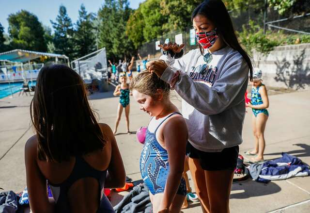 Instructor Sophia Riva helps put Sydney Tumilty's hair in a ponytail at the camp at Campolindo High.