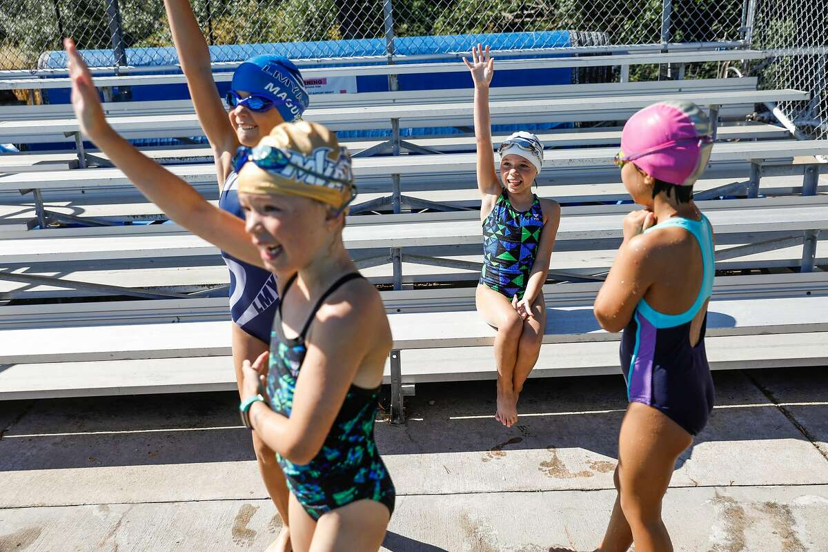 (L-r) Emily Maguire, 8, Gwen Muldoon, 8, Scarlett Benbow, 8 and Alexa Wo, 8, play a game during swim camp at Soda Aquatic Center at Campolindo High School in Moraga, California on Thursday, July 2, 2020.