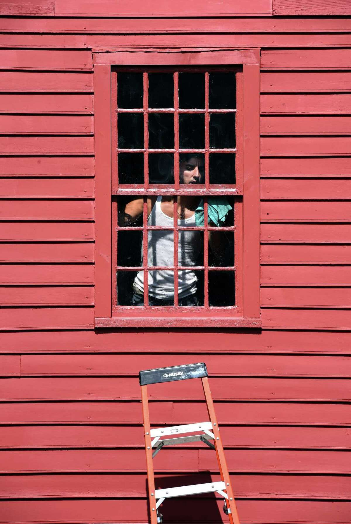 Robert Skehan of K&R Remodeling & Home Improvement cleans a rebuilt window on the Bryan-Downs House at the Milford Historical Society on August 31, 2018. The company rebuilt windows and doors, replaced trim and siding on the bottom half of the house, power washed the roof and painted the entire historic house.