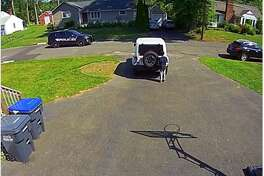 """Eliah Pierre-Louis, 9, stands behind a family vehicle in his driveway as a police cruiser drives by his home. Pierre-Louis was playing basketball. When asked later by his father why he stood behind the vehicle, Eliah said """"Because they killed George Floyd."""""""