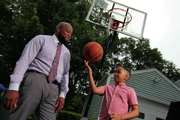 Stacey Pierre Louis and his son Eliah, 9, at their home in Trumbull on Friday. On a home security video, Eliah momentarily hid from a Trumbull police cruiser while he was playing basketball in his driveway. Stacey posted the video on Instagram and it has 65 million views.