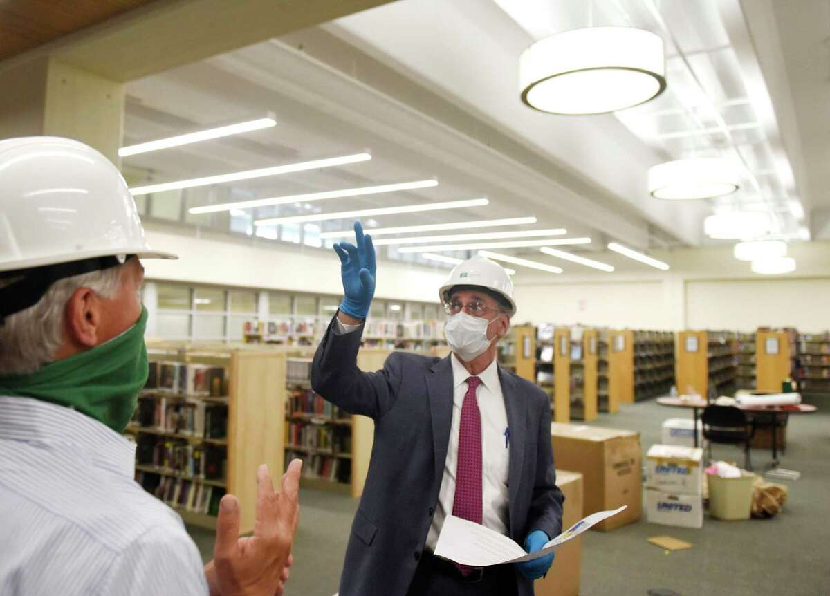 Ashforth Company Executive Vice President Hank Ashforth, left, and project manager Thomas Heagney tour the nonfiction stacks as part of the renovation construction project at Greenwich Library in Greenwich, Conn. Thursday, June 25, 2020. The library has been closed during the coronavirus outbreak, so the renovation project has been able to move forward ahead of schedule and is expected to be done before the end of 2020.