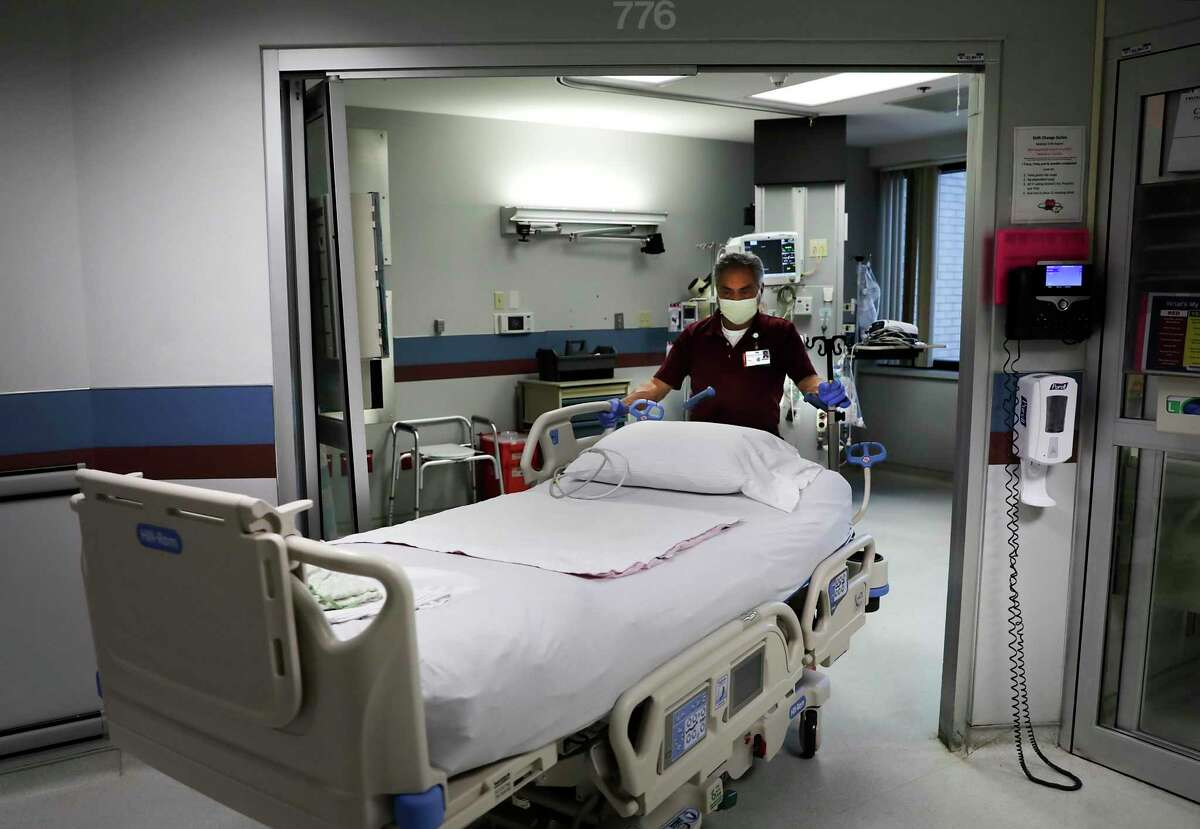 A maintenance worker wheels a bed into a room that is being prepared for a COVID-19 patient at Methodist Hospital.