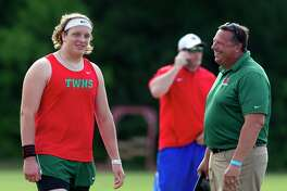 The Woodlands' Patrick Priperi jokes with coach Gary Madore between shot put throws during the District 12-6A high school track meet at College Park High School in 2018 in The Woodlands.