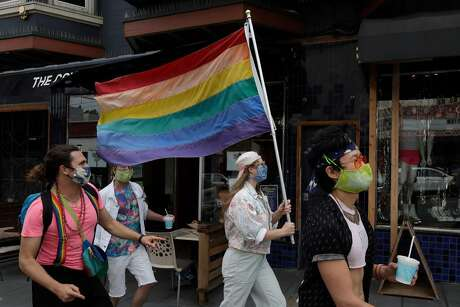 Zina Goodall carries a rainbow flag while walking with friends in the Castro district to celebrate Pride last weekend.