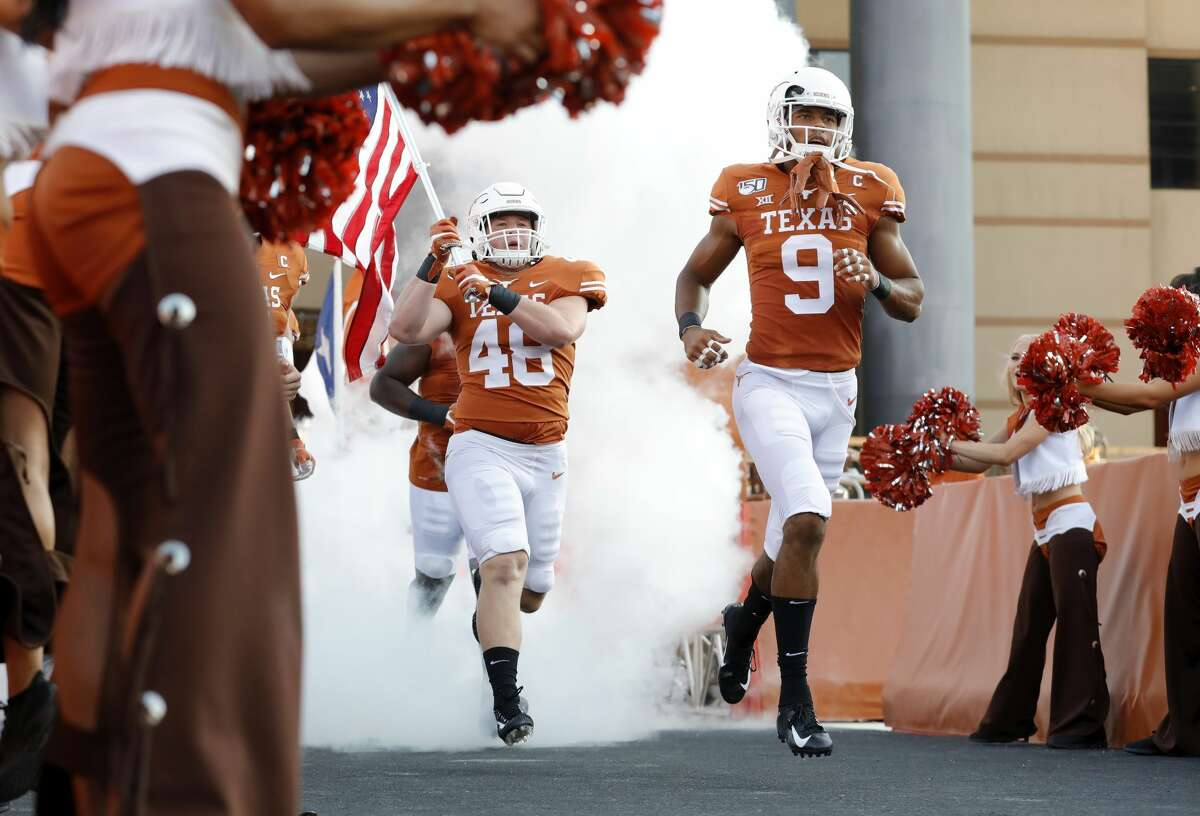 Collin Johnson #9 of the Texas Longhorns and Jake Ehlinger #48 enter the stadium before the game against the Louisiana Tech Bulldogs at Darrell K Royal-Texas Memorial Stadium on August 31, 2019 in Austin, Texas.