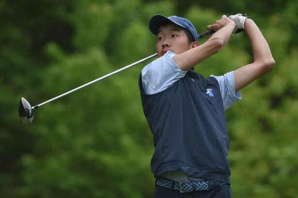 Darien's Alex Gu follows the flight of the ball during the FCIAC championships at Fairchild Wheeler Golf Course in Fairfield in 2019.