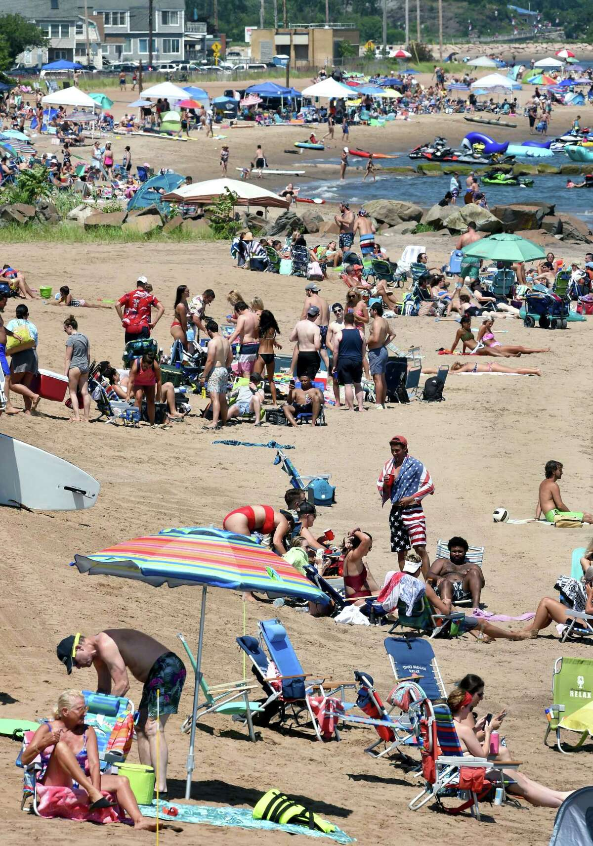 People escape the heat at the beach off of Ocean Avenue in West Haven on July 4, 2020.