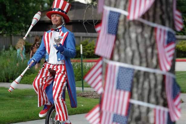 Roly Gutierrez rides a unicycle dressed a Uncle Sam on Saturday in Shenandoah.