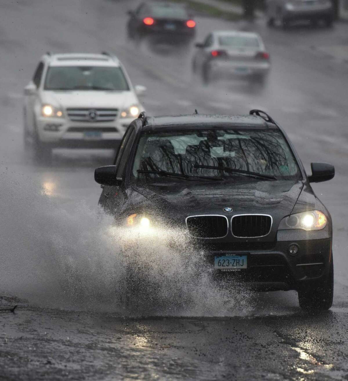 File photo of a vehicle driving through a puddle along Post Road in the Riverside section of Greenwich, Conn., taken on Monday, April 20, 2015.