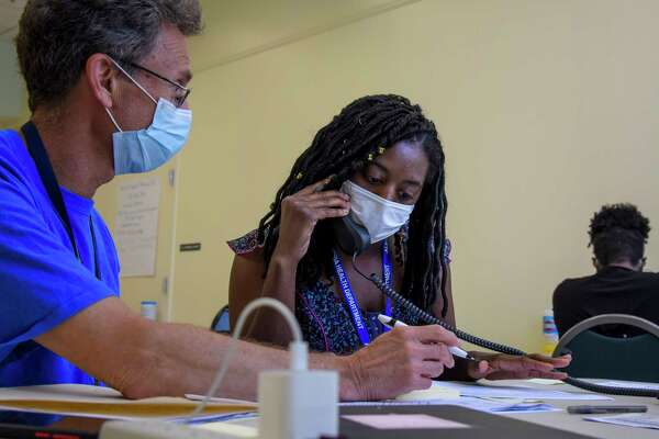 Michael Spatz, left, a volunteer with the Alexandria Medical Reserve Corps, helps AshaLetia Henderson through her first positive-case call as a coronavirus contact tracer in Alexandria, Va., in late June.