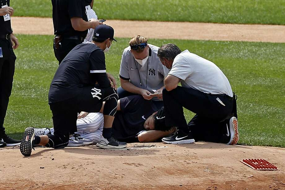 Yankees trainers attend to pitcher Masahiro Tanaka after he was hit in the head by a ball off the bat of Giancarlo Stanton at Yankee Stadium. Photo: Adam Hunger / Associated Press
