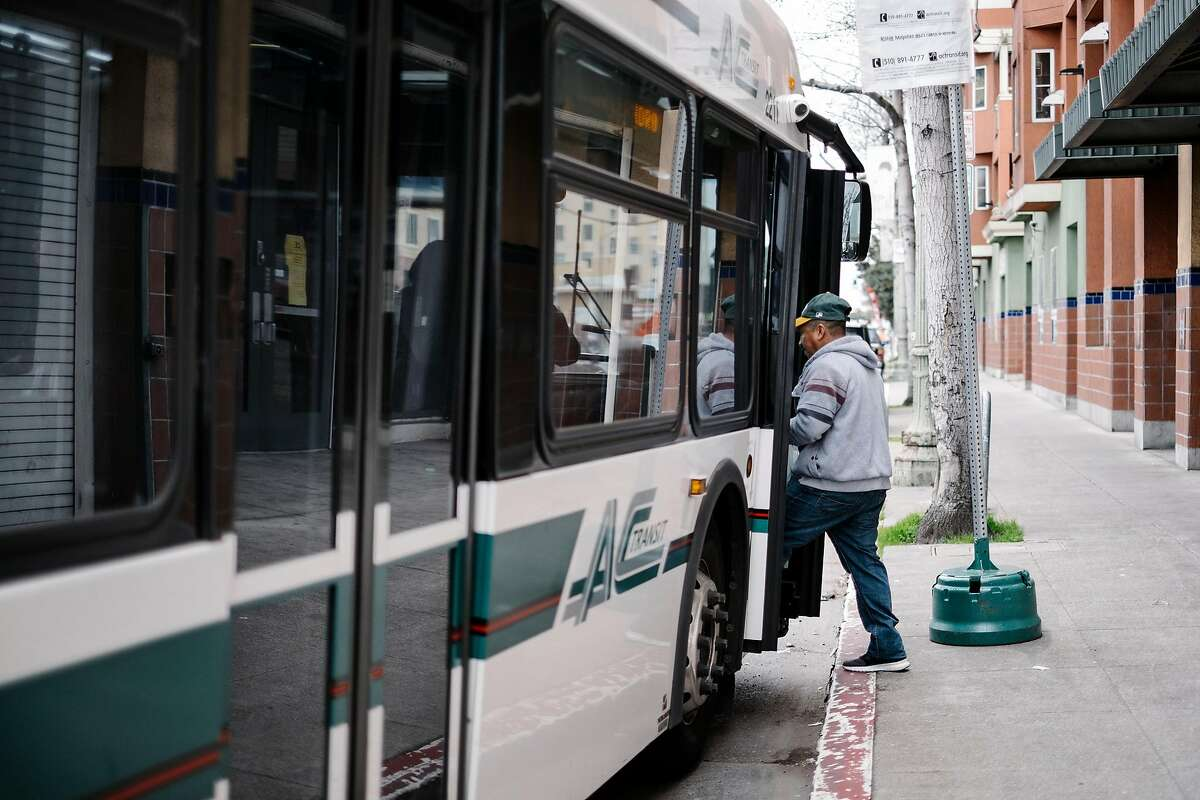 A man catches an AC Transit bus on International Boulevard where construction of the new Bus Rapid Transit(BRT) line is ongoing, in Oakland, Calif., on Tuesday, February 12, 2019.