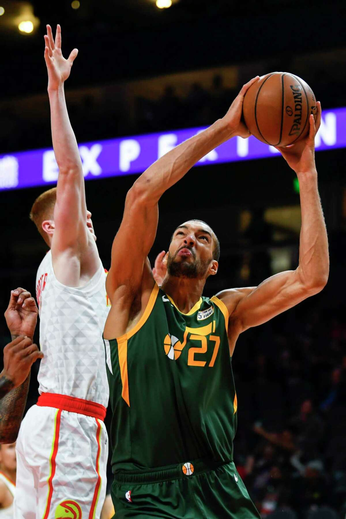 Utah Jazz center Rudy Gobert (27) shoots as Atlanta Hawks guard Kevin Huerter defends during the first half of an NBA basketball game Thursday, March 21, 2019, in Atlanta. (AP Photo/John Amis)