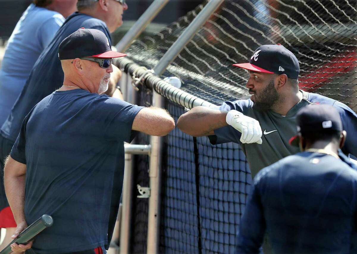 Atlanta Braves manager Brian Snitker gets an elbow bump from outfielder Marcell Ozuna during baseball practice, Friday July 3, 2020 in Atlanta. (Curtis Compton/Atlanta Journal-Constitution via AP)