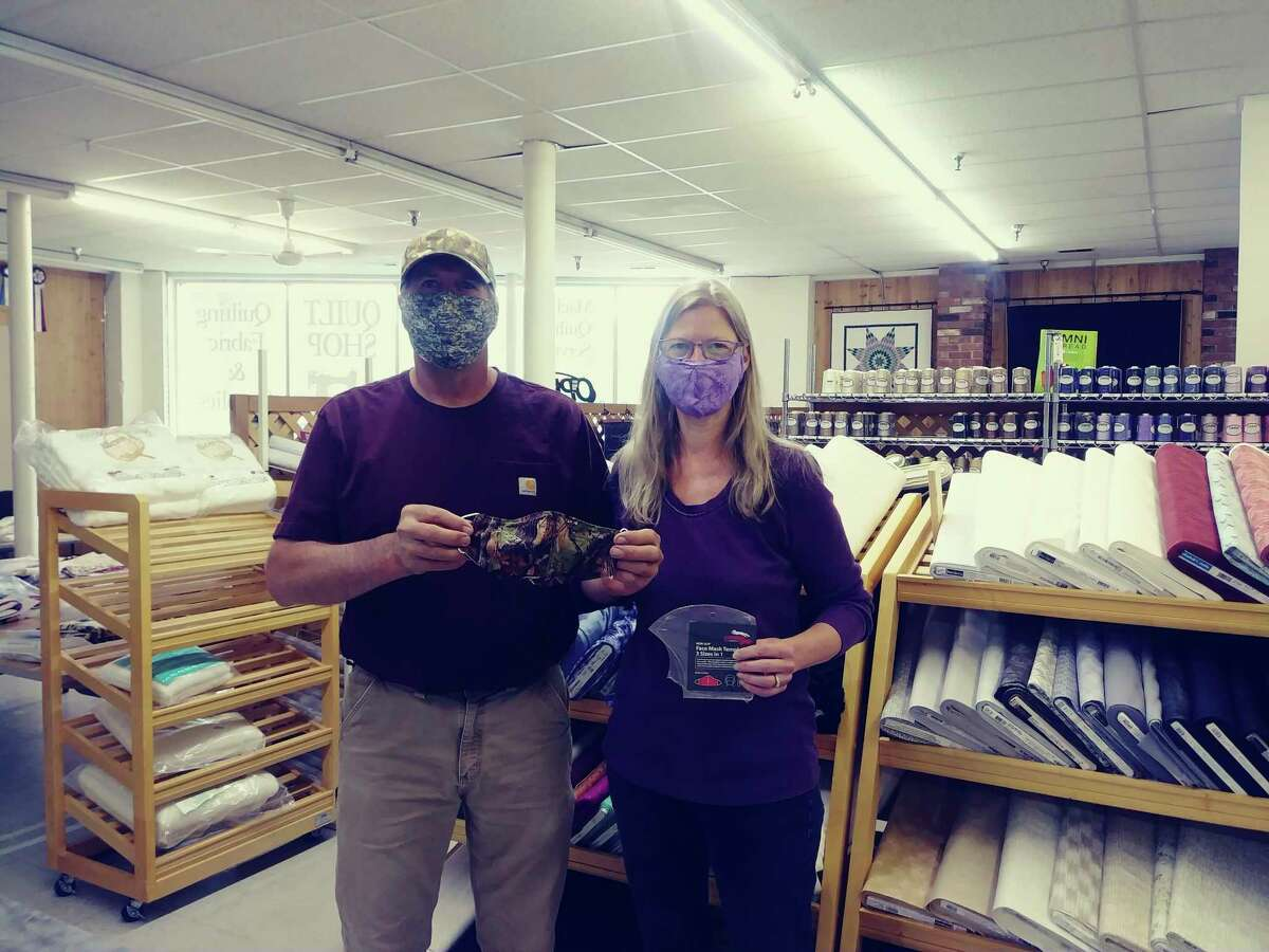 Tammy and Todd Oberlin, owners of TK Quilting in Manistee, show off mask patterns and fabric available in their store. Free fabric and elastic is available as part of a grant. (Courtesy photo)