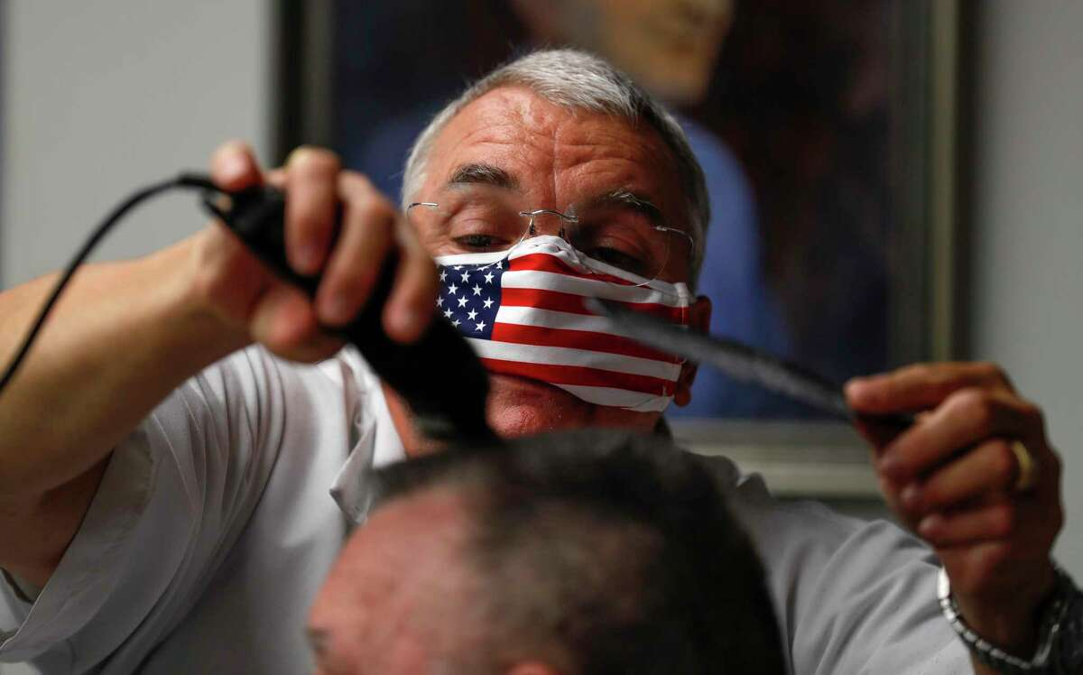 Owner Leon Apostolo carefully shapes a flat top for a customer at Shepard's Barber Shop, Friday, May 8, 2020, in Conroe. Gov. Greg Abbott modified his initial executive order to reopen the Texas economy on Tuesday to allow barbershops, nail salons and hairdressers to reopen Friday with some social distancing and hygiene protocols.